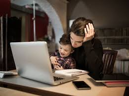 woman holding crying baby while trying to work on computer is not a good work boundary