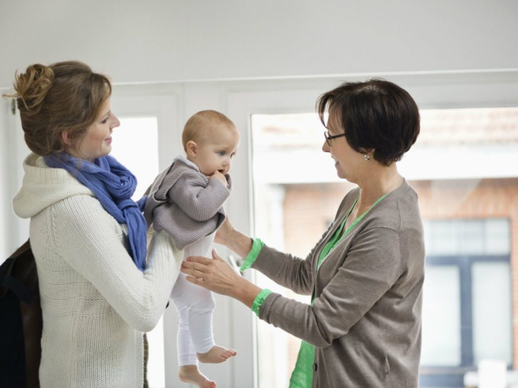 Mom handing baby to nanny to watch while she completes her workday helps to keep sanity and peace