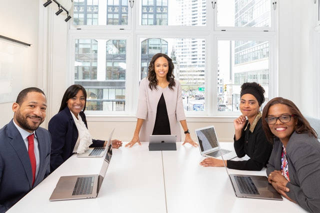 Woman standing at the head of table where 4 others are seated with their laptops open