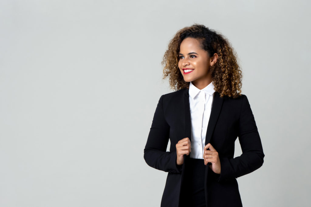 Cheerful African American business woman in black suit