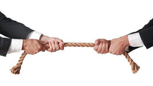 Rope with two business men pulling on each end as if in a game of tug-of-war