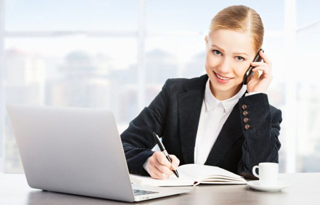 Woman talking on phone while facing lap top and taking notes on paper