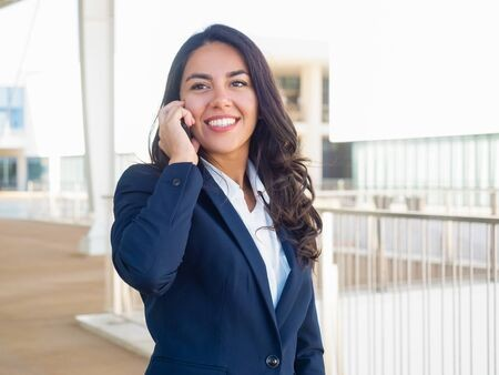 Woman in blue business jacket with white blouse, talking on cell phone.
