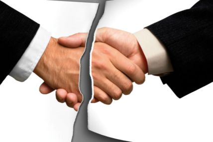 Man hands shaking on an agreement - showing their shirts are white and jackets are professional black. Line between hands showing agreement is broken