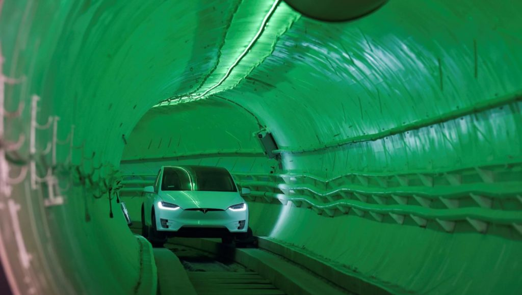 Tesla vehicle driving through a tunnel underground.