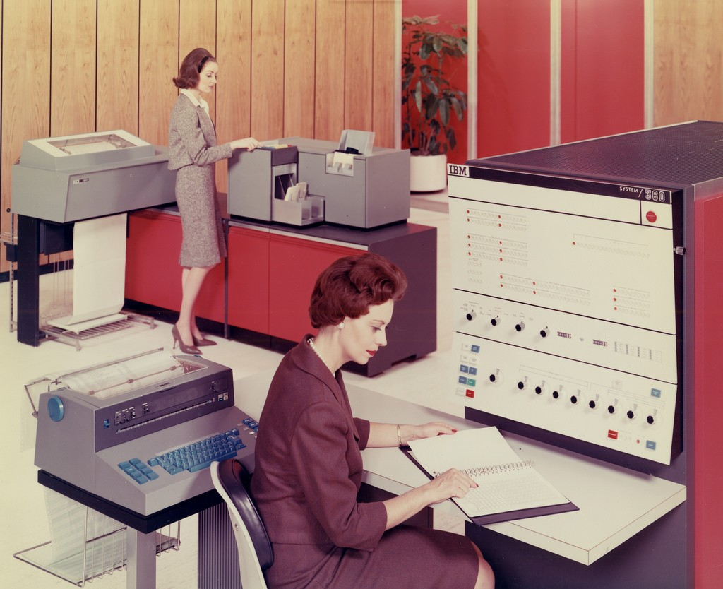 2 women in an aged photo wearing business suits from 1950's working on computers