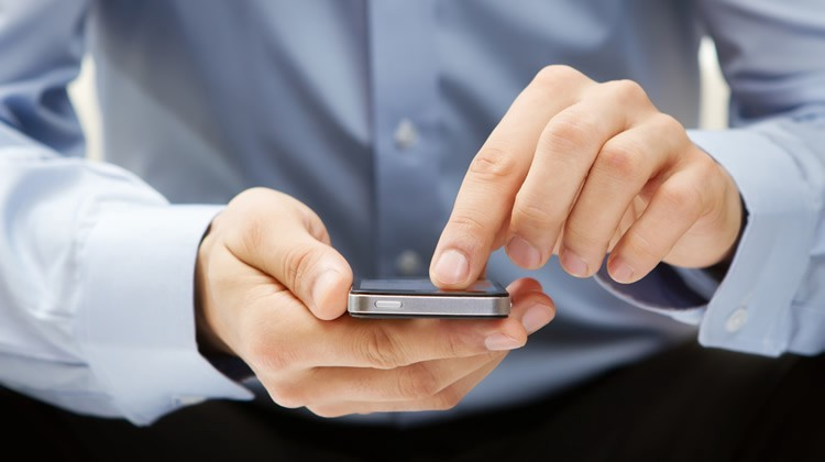Blue business shirt with hands holding a cell phone while scrolling on the phone.