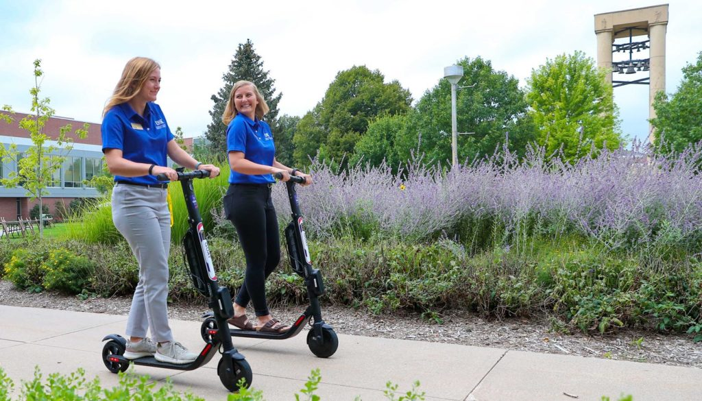 Two young women riding eScooters on a college campus