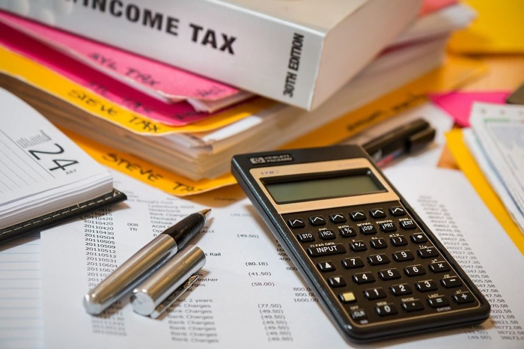 files and a book on income tax lay on a table that contains a calculator and pens.